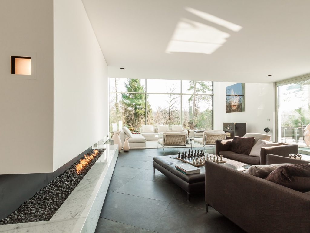 Modern Fireplaces For Inviting Interiors this six bedroom villa in brussels ha a cut in stone fireplace underneath a glass enclosed walkway 1024x768